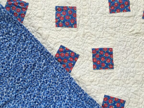 Blue floral vine fabric on back of baby quilt
