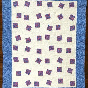 Baby quilt featuring Red floral fabric set into white background with blue borders
