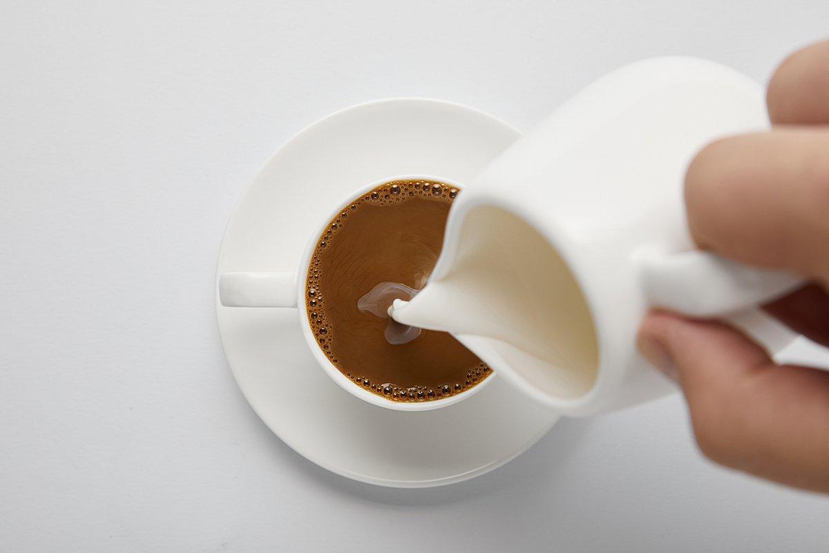 Person pouring cream into coffee