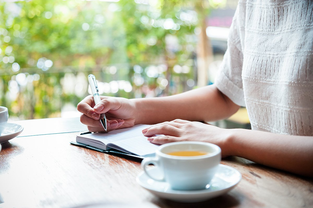 Person sitting at table and writing in journal