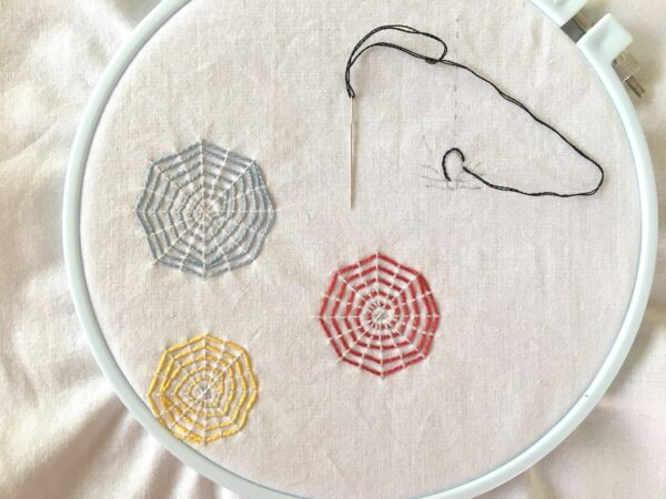 Colorful Webs and embroidery project featuring a spider and three webs in an embroidery hoop