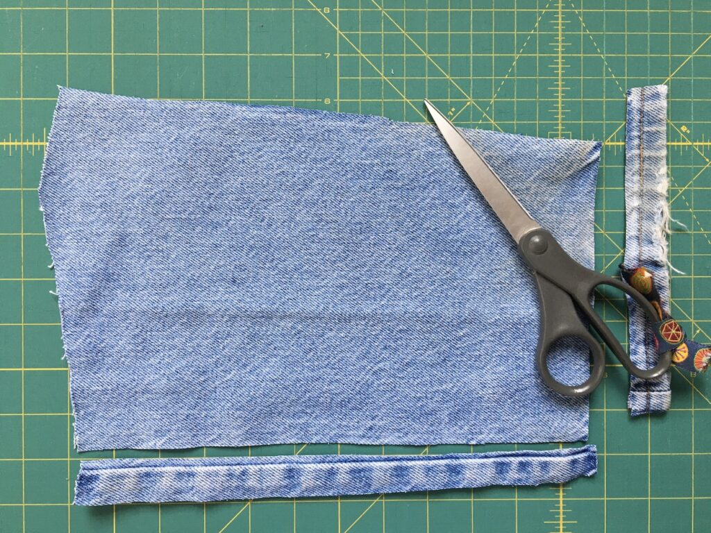 Trimming away seams on old jeans being used in project