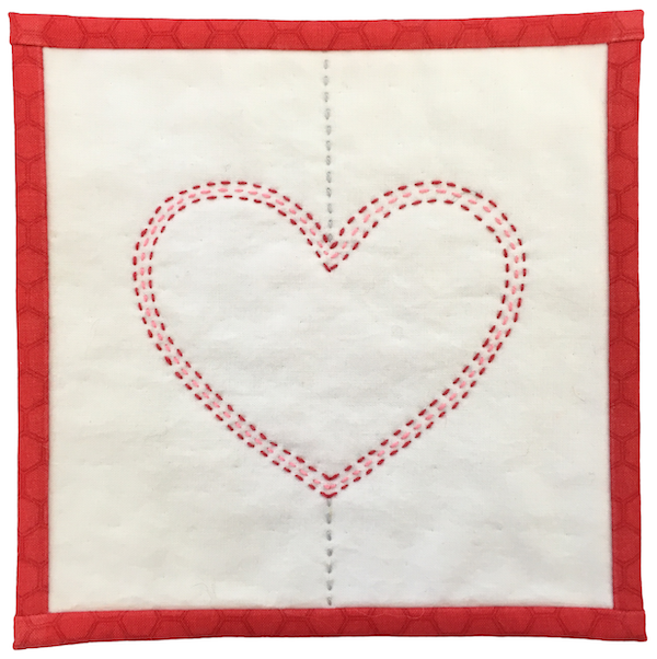 Pink and Red Concentric Quilted Hearts on White Fabric