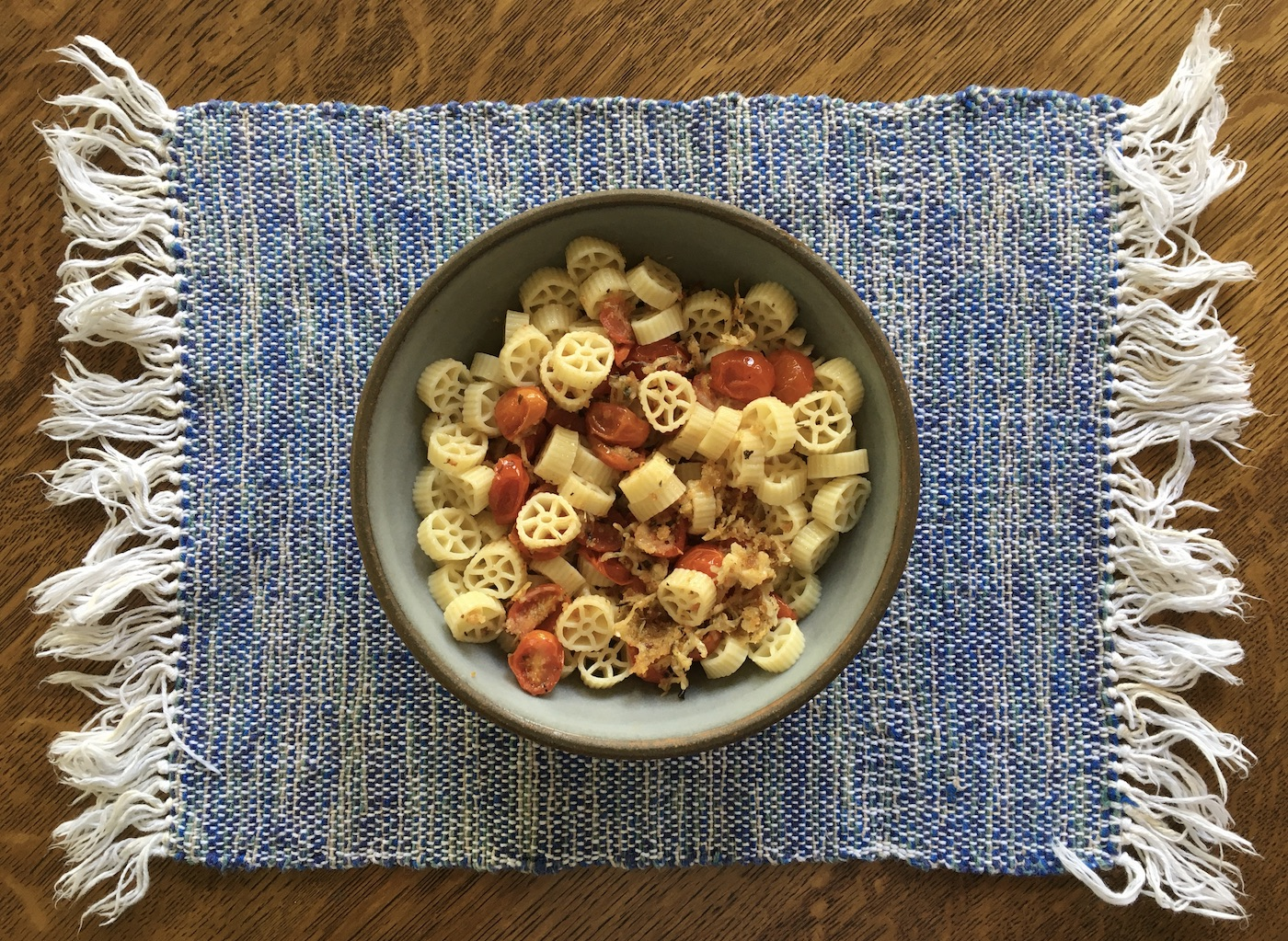 Pasta with roasted tomatoes in pottery bowl