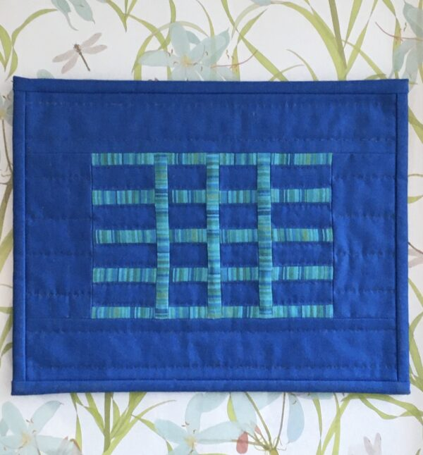 Hammock quilt displayed in front of floral wallpaper
