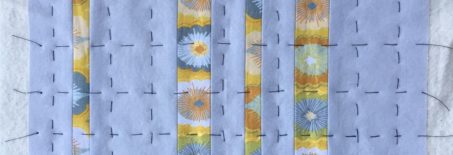 Grey and yellow quilt that is basted together with black thread