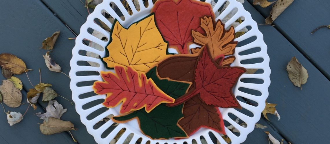 Felt leaves on white cake stand