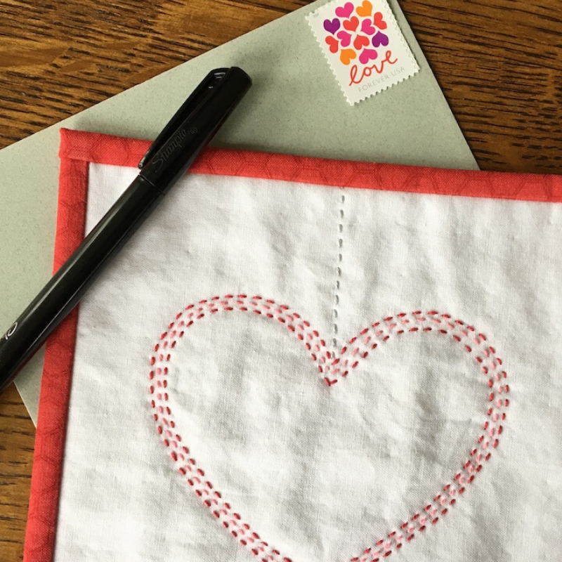 Completed Connected Hearts Mini Quilt with envelope and pen