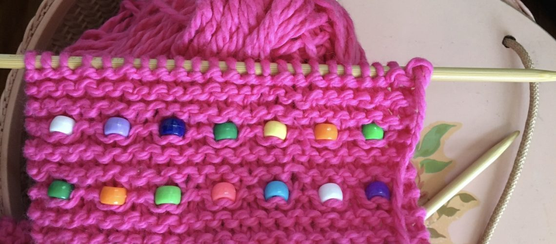 Pink knitted scarf with beads laying on sewing basket